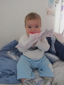 small baby eating paper